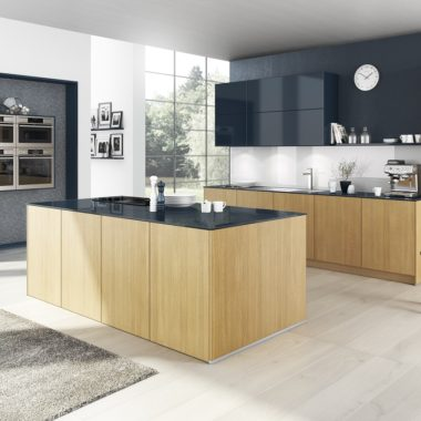 modern handleless kitchen without toe-kick in light oak wood and contrasting high gloss navy blue finish